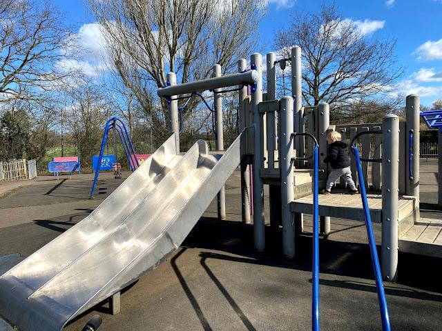A toddler on a climbing frame heading towards a slide