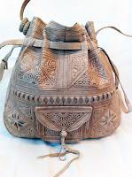 Açık krem renkli mat derisi üzerinde baskılı desen ve işlemeler olan otantik bir maroken çanta