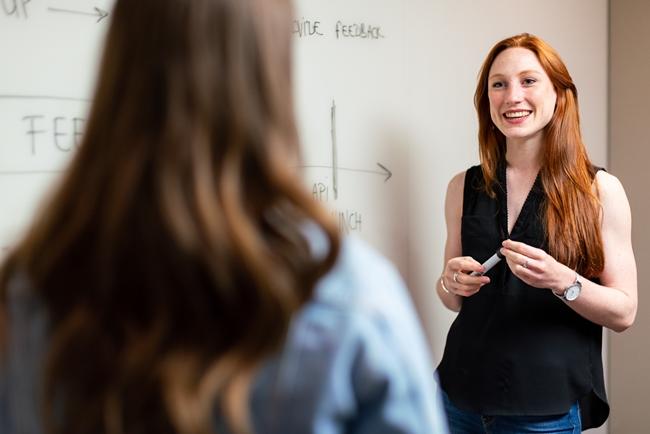 Mulher branca ruiva professora em pé sorrindo para uma aluna de costas
