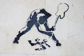 Image of graffiti art showing a person smashing a swastika with a guitar.