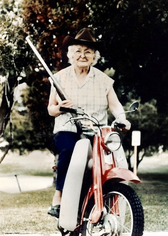 snapshot of grandma with a rifle, riding on a scooter while wearing a cowboy hat. Good Heavens and Other stories of Matronly Women. marchmatron.com