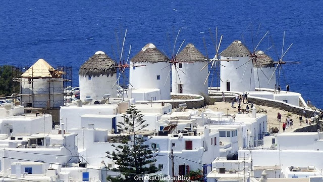 Białe majestatyczne wiatraki Mykonos. Błękitne greckie morze. Cykladzka architektura.