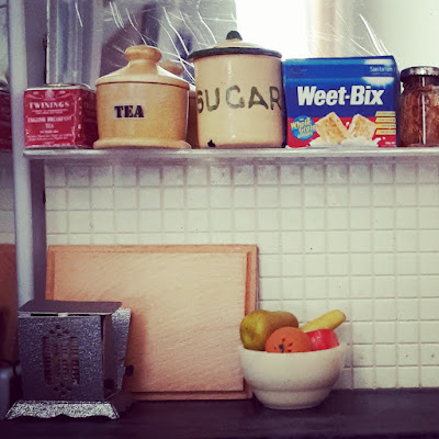 1/12 scale modern miniature scene of a kitchen bench with a fold-down toaster, chopping board and bowl of fruit on it. On the shelf above are two containers of tea, a cannister of sugar, a packet of Weet-Bix and a half-used jar of jam.