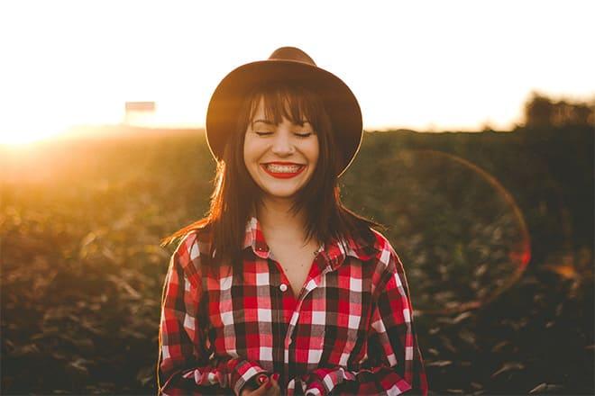Mulher de chapéu, de cabelo médio com franja, roupa de cowgirl, sorrindo