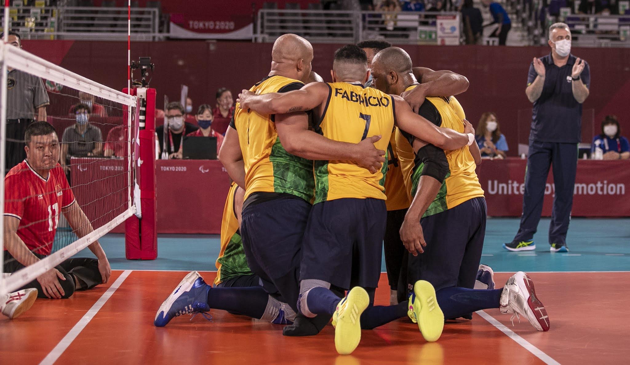 Os jogadores do Brasil, vestidos de amarelo, se abraçam no meio da quadra em comemoração a um ponto. São seis jogadores, que estão numa quadra de piso laranja. O jogador Fabrício, com a camisa número sete, aparece no meio da imagem