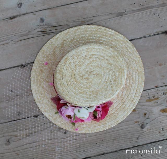 Canotier con flores rosas sobre suelo de madera antiguo, visto desde arriba