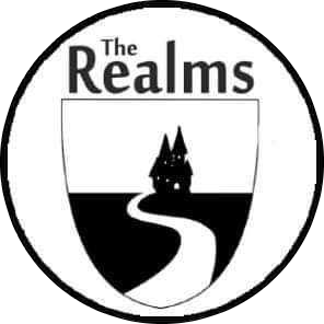 "A circular white bade with a black border. At the top of the badge is written the words ""The Realms"" in black text. The center of the badge shows a path leading up to a small black castle."