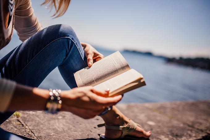 Mulher lendo um livro numa calçada na beira do mar ou de um grande lago. Ela usa calça jeans, sandália de dedo sem salto, esmalte claro e pulseiras prateadas. O rosto dela não aparece na foto.