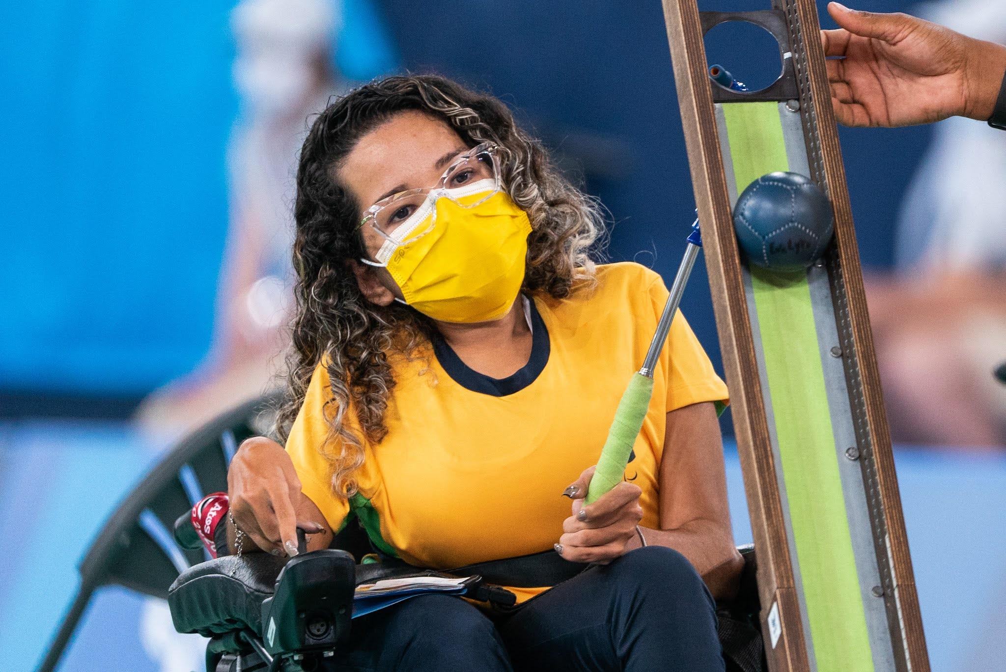 Evelyn Oliveira, de máscara e na cadeira de rodas, coloca uma das bolas na calha