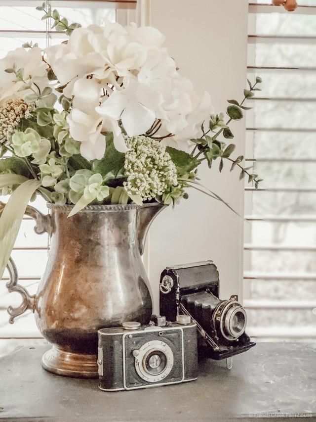 White hydrangea bouquet in a vintage silver pitcher