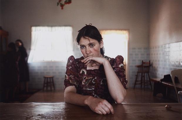 Retrato de una adolescente frente a una mesa. Es el interior de una habitación casi vacia, hay 2 sillas al fondo y un par de ventanas donde entra algo de luz.