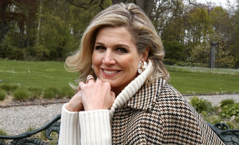 Queen Maxima wore a houndstooth cape by Saint Laurent, and white high neck sweater pullover by Zara, H&M, and floral earrings by Zara