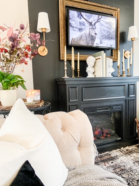 black fireplace with gold sconces