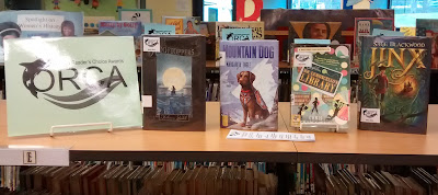 Books arranged upright and facing forward on a library countertop. At the far left, a sign next to the books proclaims, 'ORCA' with a pictorial representation of the orca whale. Smaller letters above the logo read, 'Oregon Reader's Choice Award.' From left to right on the countertop, the books are 'Rooftoppers' by Katherine Rundell, 'Mountain Dog' by Margarita Engle, 'Escape from Mr. Lemoncello's Library' by Chris Grabenstein and 'Jinx' by Sage Blackwood