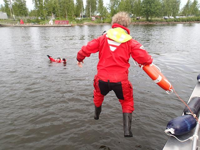 Henkilö hyppäämässä pelastautumispuvussa veteen pelastusrenkaan kanssa, taustalla huitoo toinen pelastautumispukuinen henkilö vedessä