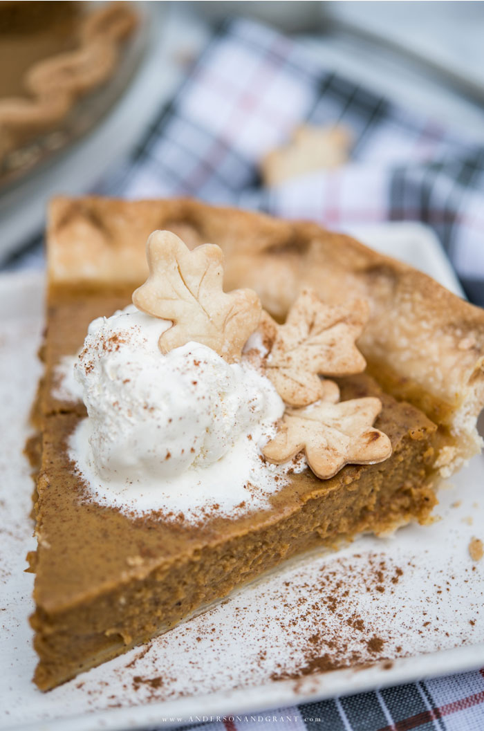 Slice of pumpkin pie with whipped cream and leaf shaped dough garnish.