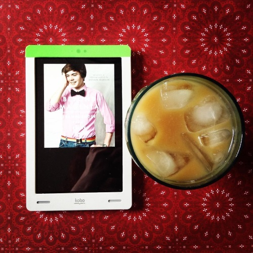 An overhead shot of a white Kobo sitting to the left of a glass of iced coffee. The Kobo's screen holds the cover of Beyond Magenta, featuring a brunette white boy wearing a pink shirt with a black bow tie, jeans, and a rainbow belt.