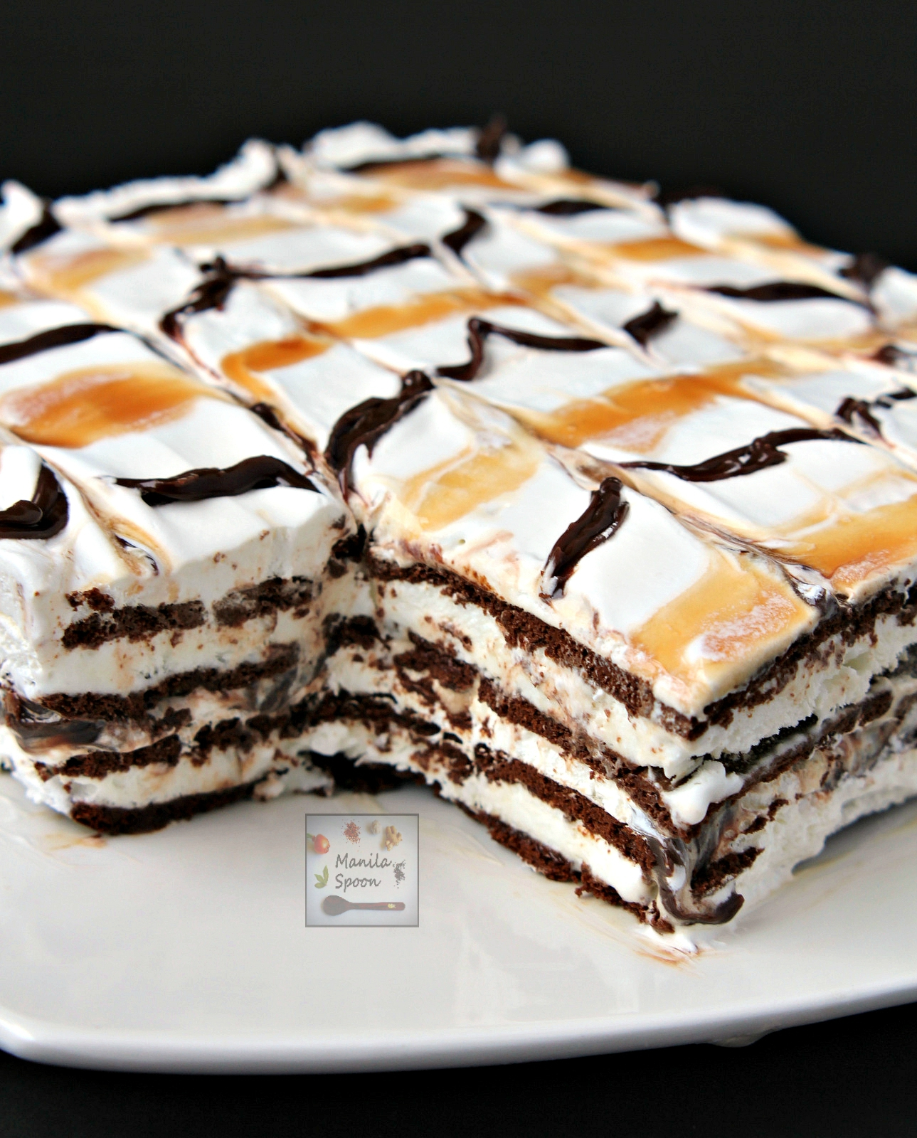 Layers of your favorite ice cream sandwich, whipped cream, chocolate fudge and caramel sauces and sprinkled with nuts (and some more sauce on top!) - this Lazy Ice Cream Sandwich Cake is summer's yummiest treat! Did I mention it is crazy EASY to make?