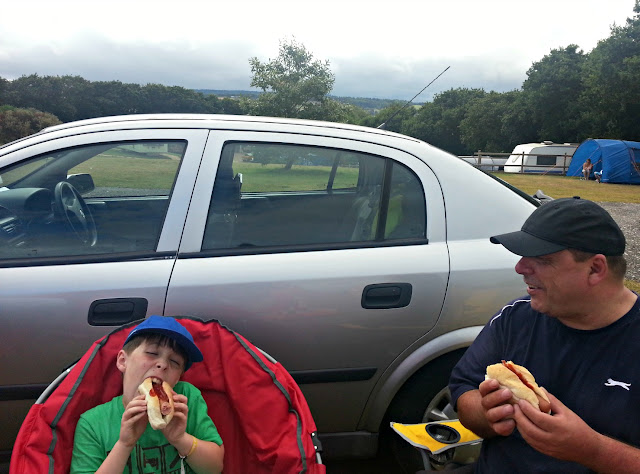 Father and son enjoying hotdogs next to car