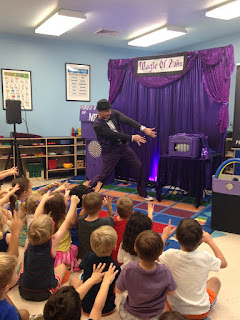 kids magician zain wiggeling fingers at a magic trick in purple suit