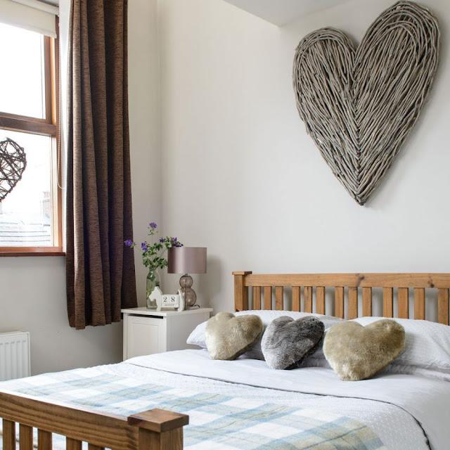 Kamar tidur putih kecil dengan tempat tidur kayu tirai cokelat dan dekorasi dinding hati anyaman
