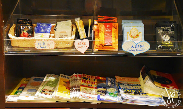 shelf with tea packets, bathing powder, and travel brochure