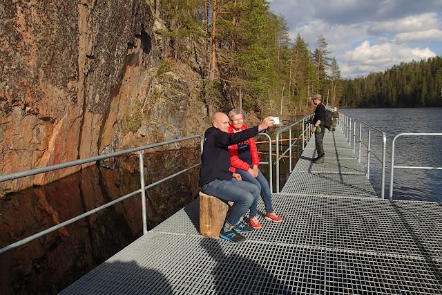 Kaksi henkeä ottamassa selfietä pystysuoran kallion edustalla kelluvalla kävelysillalla