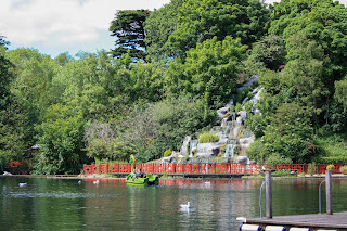 A lake with an island with oriental style waterfall and fencing