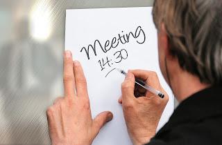 Ein Mann notiert mit einem Stift einen Gesprächstermin auf einem Zettel