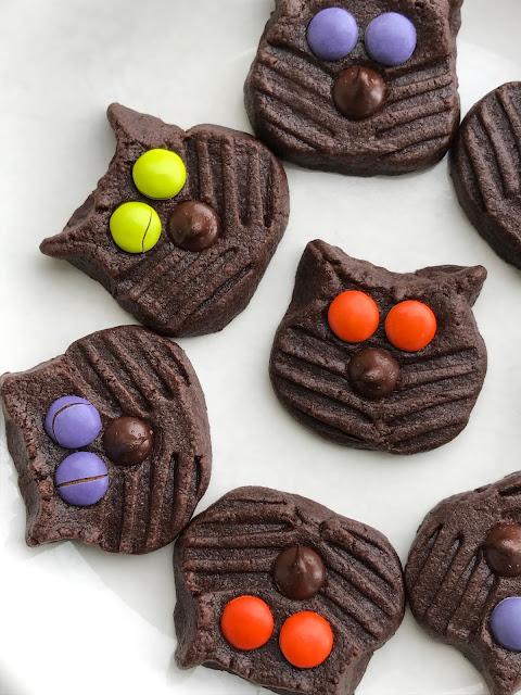 Black cat cookies with purple, green, and orange eyes.