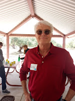 A man with grey hair, dark sunglasses and a red shirt standing under a ramada