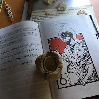 A open book with chant on one side, a black and white drawing of the evangelist St. Mark with a lion. A small white clay hemisphere sits on the right hand page.