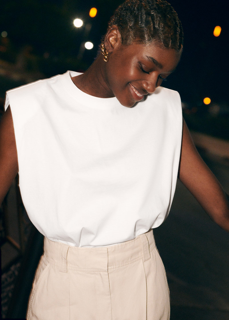 minimalist summer going out look inspiration white padded-shoulder top and high waisted tan pants