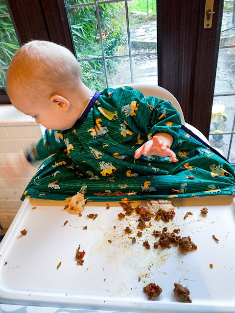 A photo of a baby in a highchair with food all over the tray. He is looking at the floor on the side of the highchair and waving his hand fast (it is blurred)