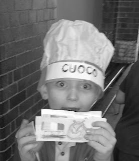 Black and white photo of young boy with money and a chef's hat