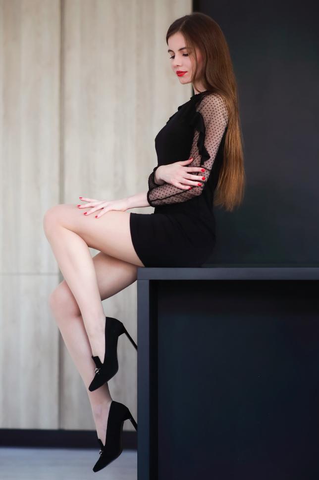Czarna obcisła sukienka, cieliste rajstopy i zamszowe szpilki