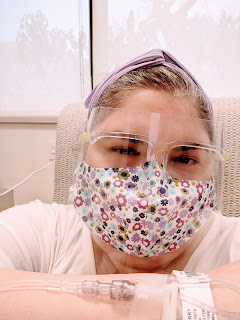 Photo of me at the infusion center, wearing a floral mask and clear face shield, holding up my arm with an IV line and hospital bracelet