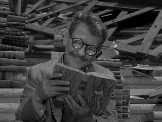 A man with thick glasses reading a book with piles of books behind him.