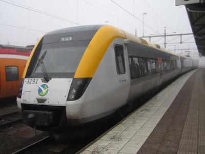 Närbild snett framifrån på gul-grått Västtrafiktåg vid perrongen.