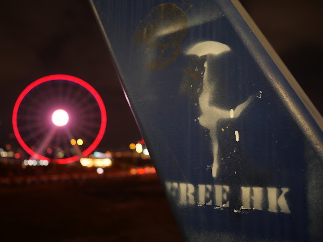 "graffiti of ""FREE HK"" and dancer holding an umbrella with the Hong Kong Observation Wheel lit up in red in the background at night"