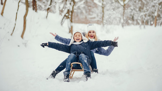 a mother and son smiling and sharing a sled