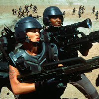 A woman and a man with futuristic guns fighting in the desert