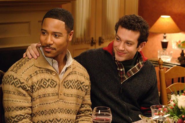 Tyrone Giordano está sentado a la derecha junto a un hombre negro. Apoya un brazo en su hombro y sonríe