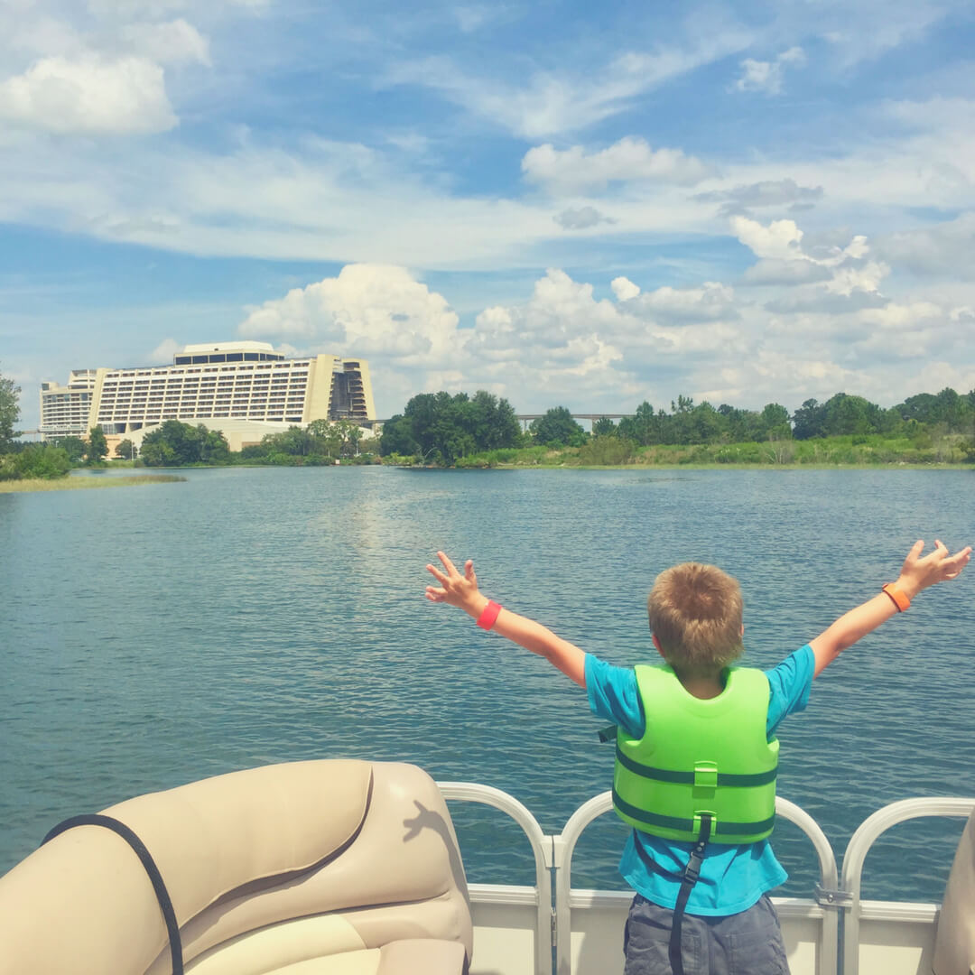 A young boy aged 6 stands on a boat on a lake in front of Contemporary Resort in Walt Disney World