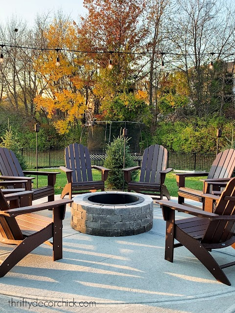 Dark brown Adirondack chairs around fire pit