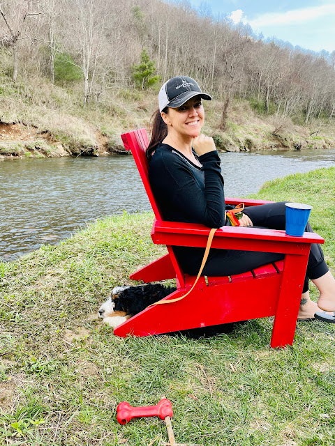 woman on a lawn chair with a puppy underneath sitting by a river