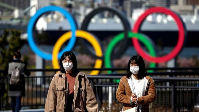 Japoneses andando com os arcos olímpicos atrás