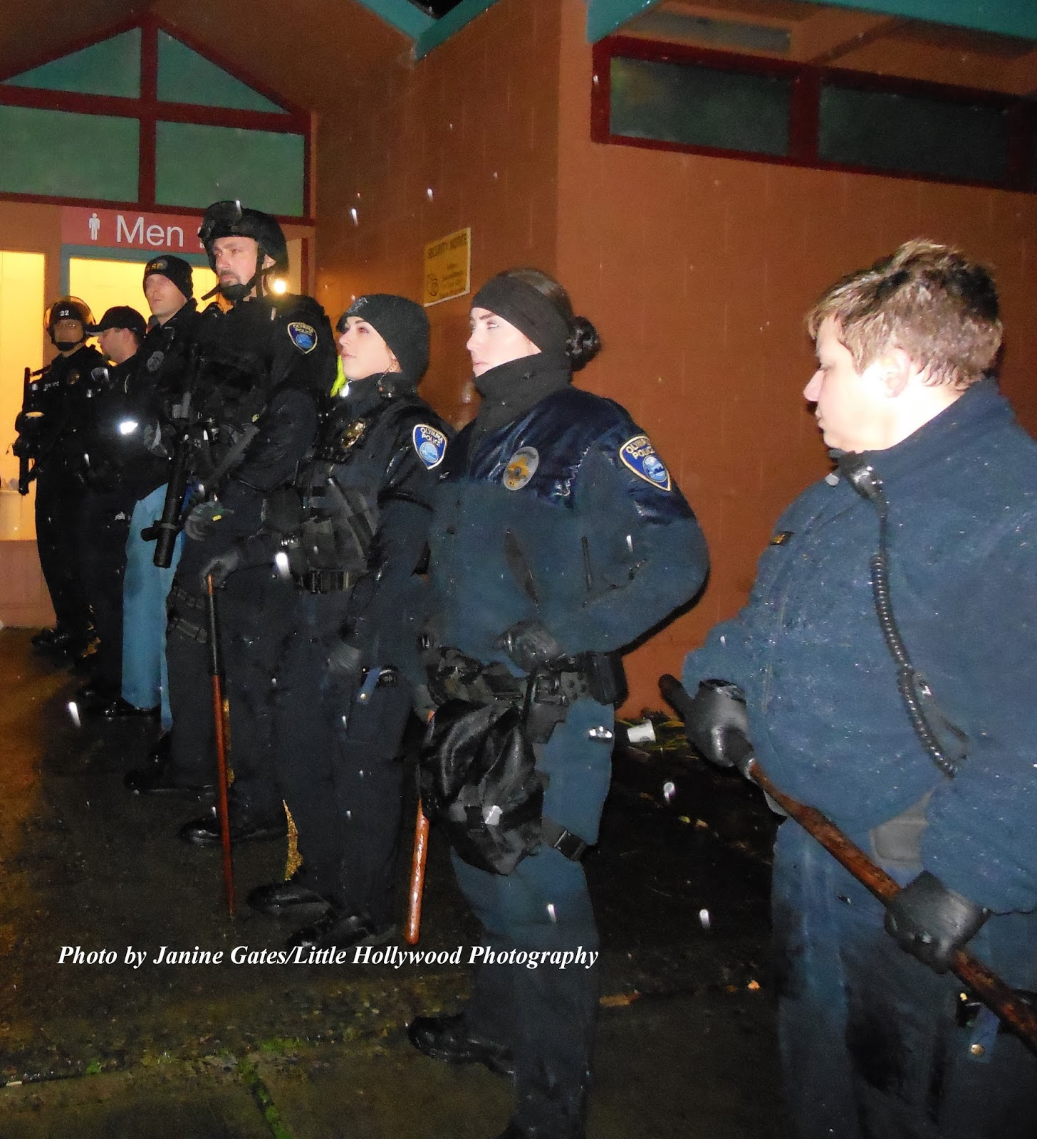 Unique Above Olympia Police Department officers armed with pepper ball guns assist Washington State Patrol officers at the Heritage Park restrooms on Monday