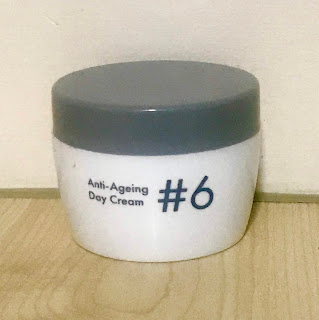 A circular white tub with #6 in big grey font with anti-aging day cream in smaller grey font with a grey circular lid on a bright background