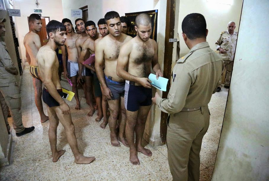 Iraqi men line up for physical examinations at the main army recruiting center to volunteer for military service in Baghdad, Iraq, Tuesday, June 24, 2014, after authorities urged Iraqis to help battle insurgents.